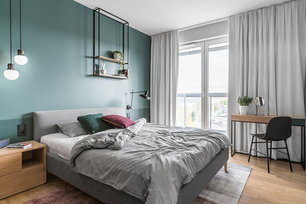 Dormitorul matrimonial este cel mai generos dintre camerele de odihnă și este tratat minimal, într-o notă contemporană. Peretele din spatele patului este unul de accent, folosindu-se nuanțe mai închise, mai relaxante, frumos combinate cu griuri plăcute. Texturile din lemn vin să încălzească totul.