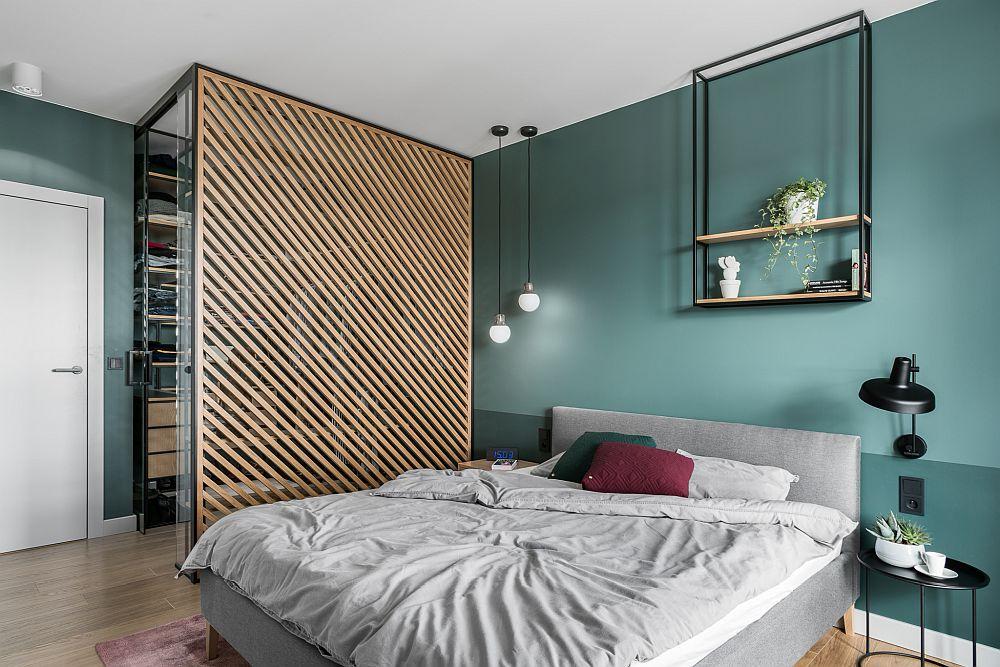 Pentru a nu încărca spațiul cu un dulap, arhitecții au prevăzut un loc de dressing separat, la fel ca și livingul, de un panoul metalic cu rifleje din lemn.