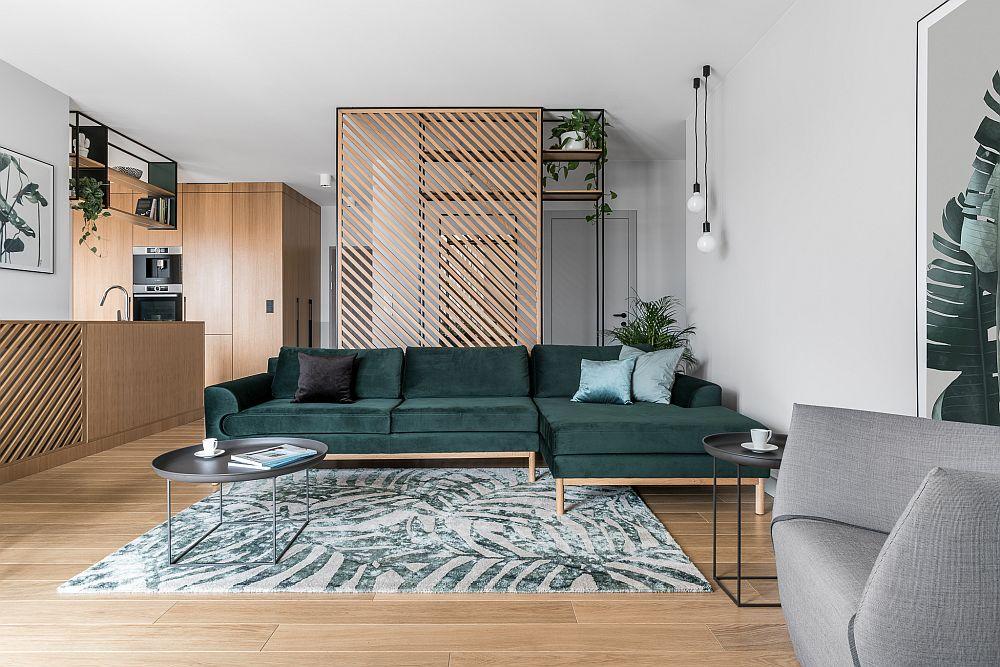Locul de luat masa coexistă în același spațiu cu livingul, unde canapeaua generoasă de la Sofacompany este cea mai amre pată de culoare. Covorul și posterul de lângă fotoliu sunt cele care creionează stilul urban jungle, alături de nunața verde a tapițeriei canapelei.