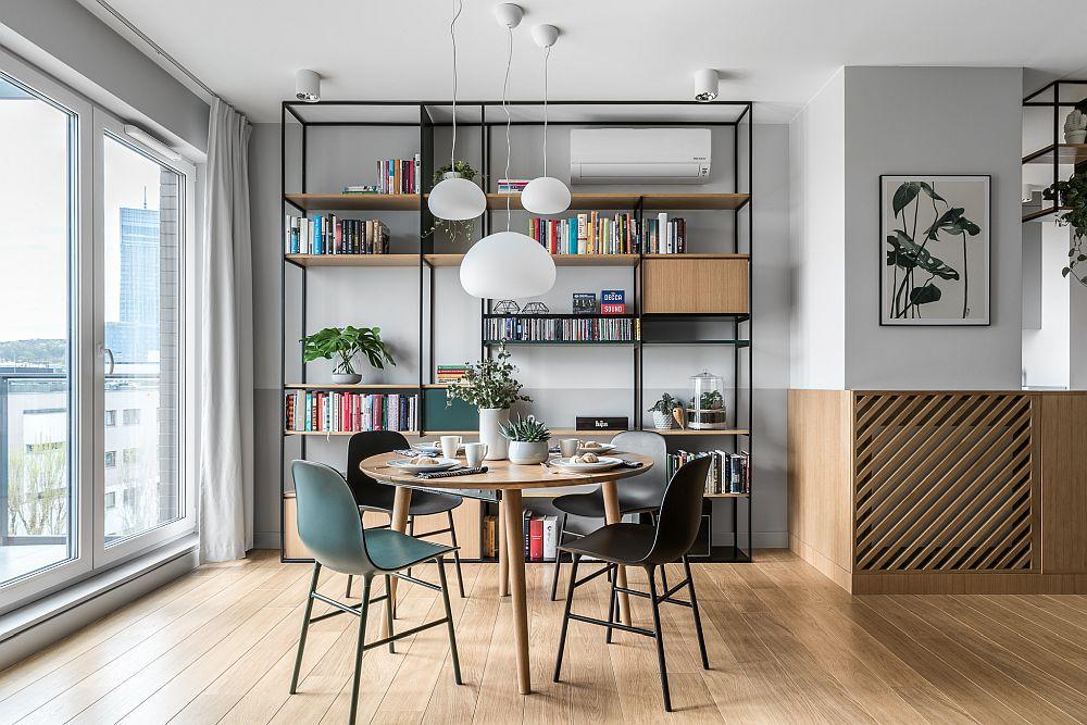 Locul de luat masa se vede încă de la intrarea în casă, ceea ce oferă un aspect primitor locuinței. De asemenea, locul de luat masa este situat aproape față de bucătărie. Mobila simplă, aerisită include în ansamblul ei și aparatul de aer condiționat, iar linia măștii de calorifer este continuată la aceeași înălțime cu o nuanță de vopsea mai închisă față de restul pereților, ceea ce echilibrează vizual spațiul. Stilul Urban Jungle este sugerat prin nuanțele de verde și prin postere cu plante, alături de ghivece cu plante decorative.