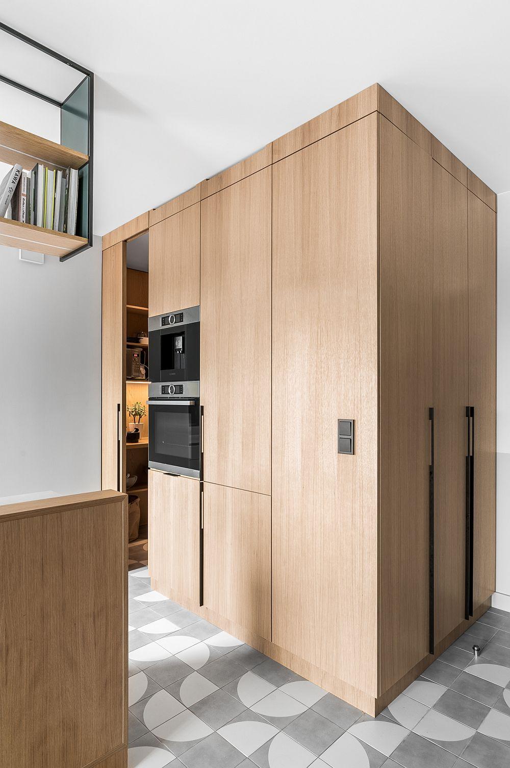 Bucătăria este configurată aproape de intrarea în casă. Pentru a exista spațiu de depozitare în hol, arhitecții au prevăzut un dulap care poate fi acționat dispre hol, iar acesta este mai departe înglobat într-un ansamblu ce include combina frigorifică încorporată, apoi cuptoarele, ar mai departe un loc de depozitare pentru zona de bucătărie.