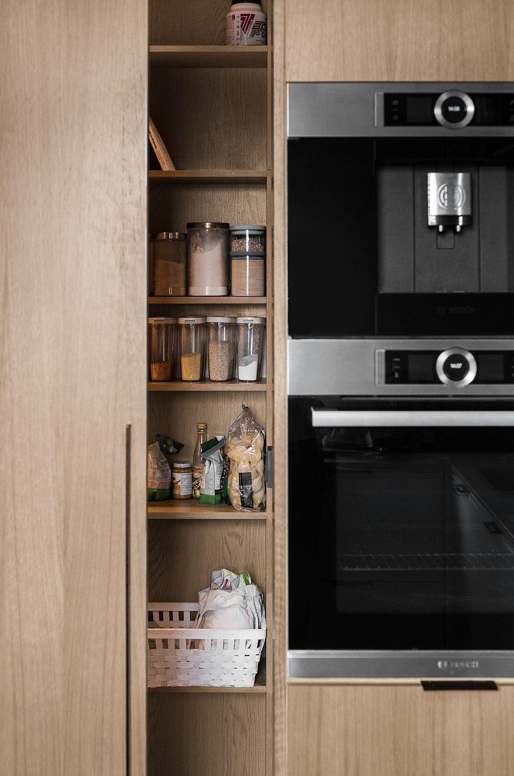 Spațiul de depozitare al bucătăriei pentru alimente și vase mai mari este gândit la un dulap generos cu ușă culisantă.