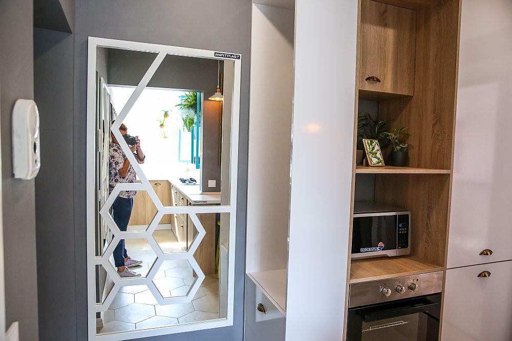 Holul de la intrare l-am tratat ca pe o extensie a bucătăriei. După ușa de la intrare, în care se vede fotografa Sorina Andreica de la ProTv, am prevăzut o oglindă realizată pe comandă la Martplast. Oglinda dă impresia de spațiu mai adânc, dar este pusă strategic și lângă cuier, deci la fix pentru o ultimă verificare înainte de a ieși din casă. Apoi, mobilierul include locul pentru cuptoare (cu microunde și de gătit) și mai departe locul pentru combina încorporată în mobilier.