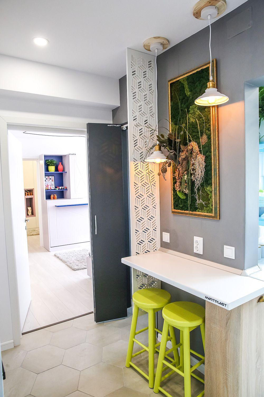 Față-n față cu mobilierul ce include electrocasnicele mari, tot în hol este un ic loc de luat masa. Locul de luat masa este marcat în lateral de un paravan din MDF traforat, dar totodată și separat față de accesul în baie. Mobila este realizată pe comandă după proiectul meu la Martplast, iar scaunele din lemn sunt de la Dedeman și vopsite de mine într-o culoare de verde măr. Deasupra locului de luat masa este un tablou cu licheni și plante stabilizate de la Arta Grădinilor. Nuanța gri de pe perete este vopsea lavabilă de la Dulux obținută la mașina de colorat. Corpurile de iluminat sunt de la Dedeman.