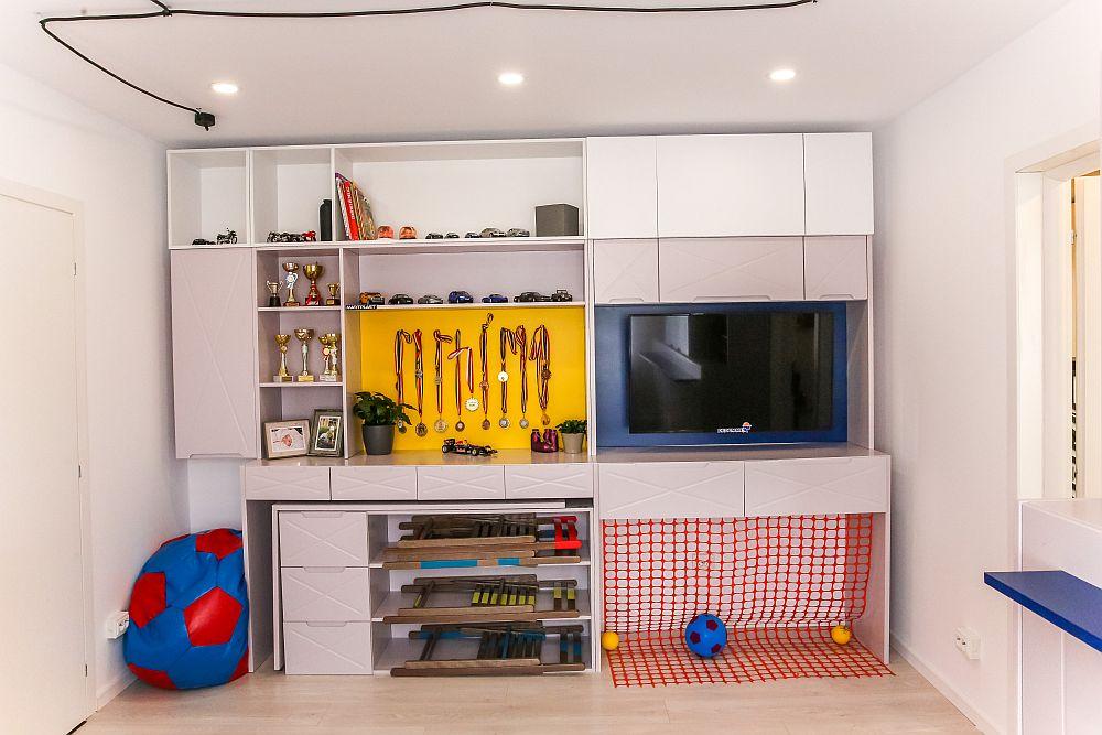 Opus față de fereastră și după ușa camerei, Ciprian a prevăzut un ansamblu de mobilier cu piese care sunt pliabile și modulare. Masa de birou poate fi trasă de sub zona cu rafturi. În partea superioară e loc pentru tv pentru medaliile și trofeele copiilor. De asemenea, aici Ciprian a făcut și proiectul lui special pentru băieți: o poartă pentru fotbal marcată de o plasă portocalie.