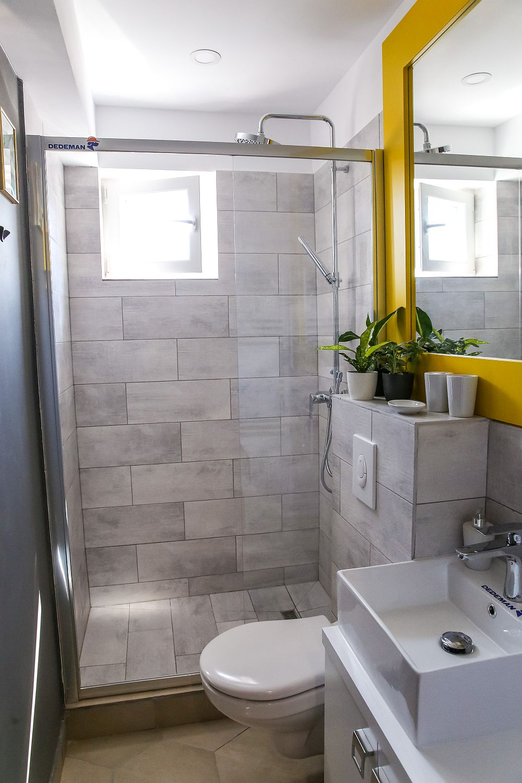 Baia, un spațiu foarte mic, dar noroc că este ventilat natural. Am prevăzut un loc pentru duș separat cu un panou de sticlă. Am mutat locul vasului de toaletă pentru că incomoda accesul în baie, iar lavoarul este chiar la intrarea în baie.