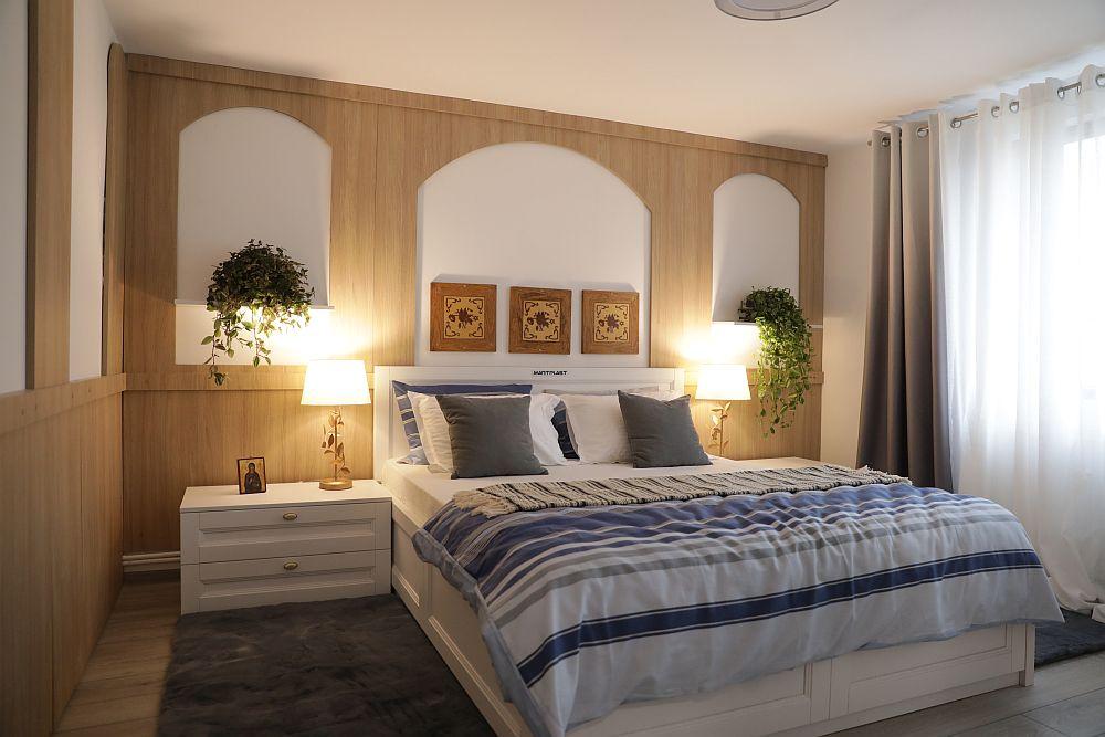 Dormitorul l-am gândit simplu, aerisit, curat, iar influențele rustice sunt ușor simțite prin placările pereților realizate cu panouri de PAL. Mobila este simplă, albă, din MDF din colecția Martplast - model dormitor Ștefan, iar decorațiunile textile, veiozele și plantele sunt de la Dedeman.