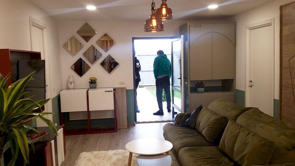 Intrarea în casă coincide cu cea în living. De o parte și de alta a intrării în casă Cristina a prevăzut o comodă și respectiv un dulap cu loc de cuier.