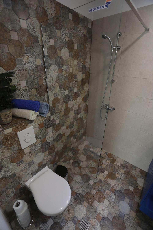 Baia DUPĂ renovarea făcută de echipa Visuri la cheie. Cristina s-a ocupat de amenajarea micuței camere. Pe perete și pe pardoseală este gresie de la Dedeman. De asemenea, obiectele sanitare, decorațiunile, prosoapele și panoul de duș sunt de la Dedeman.