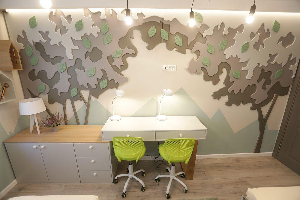 În fața paturile este locul pentru birou, dar toată zona este marcată de o placare suprapusă cu elemente din MDF care sugerează o pădure. Toată mobila și decorul de pe perete sunt realizate pe comandă la Martplast, după proiectul lui Valentin. Scaunele și veioza sunt de la Dedeman.