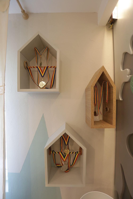 În lateralul locului de birou, Valentin a pevăzut niște cutii în formă de căsuțe pentru expunerea medaliilor copiilor.