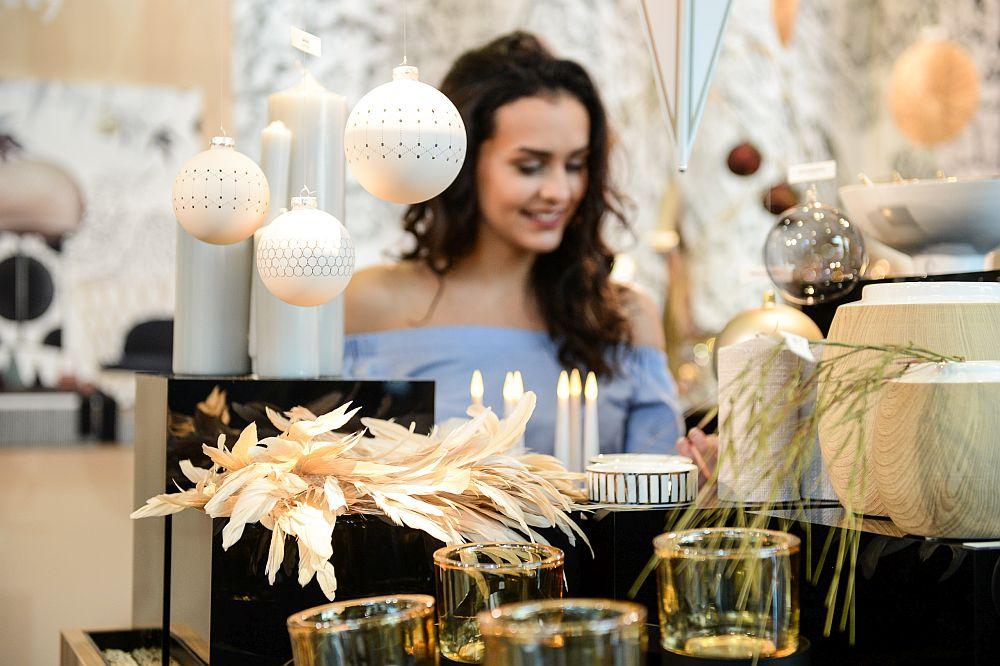 Detaliu cu globuri delicate din trendul Sobrietate echilibrată, alături de piese din sticlă fin realizate și decorațiuni din pene în nuanțe deschise, diafane.