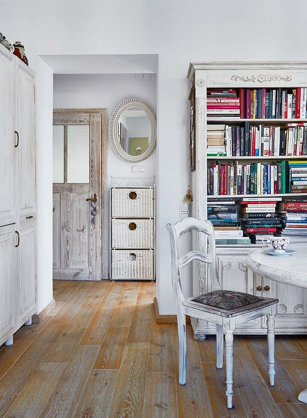 Intrarea în bucătărie este marcată cu un gol, adică fără ușă pentru că în lateralul acestuia (stânga) sunt mascate electrocasnicele mari: combină frigorifică și mașina de spălat). Proprietara a folosit un dulap actual, cu uși frezate pe care le-a patinat la fel ca și textura ușilor. Prezența cărților în bucătărie dă aspectul unei camere primitoare, care alungă caracterul tehnic al camerei. Biblioteca a fost și ea realizată dintr-o piesă veche de mobilier decorată cu ornamente din lemn și ulterior patinată (găsești ornamente din lemn la Gold House Concept). Mobila similară pe care să o poți finisa cum vrei găsești la Gold House Concept, iar piese de-a gata la Retroboutique.ro și la MaisonRomantique.ro
