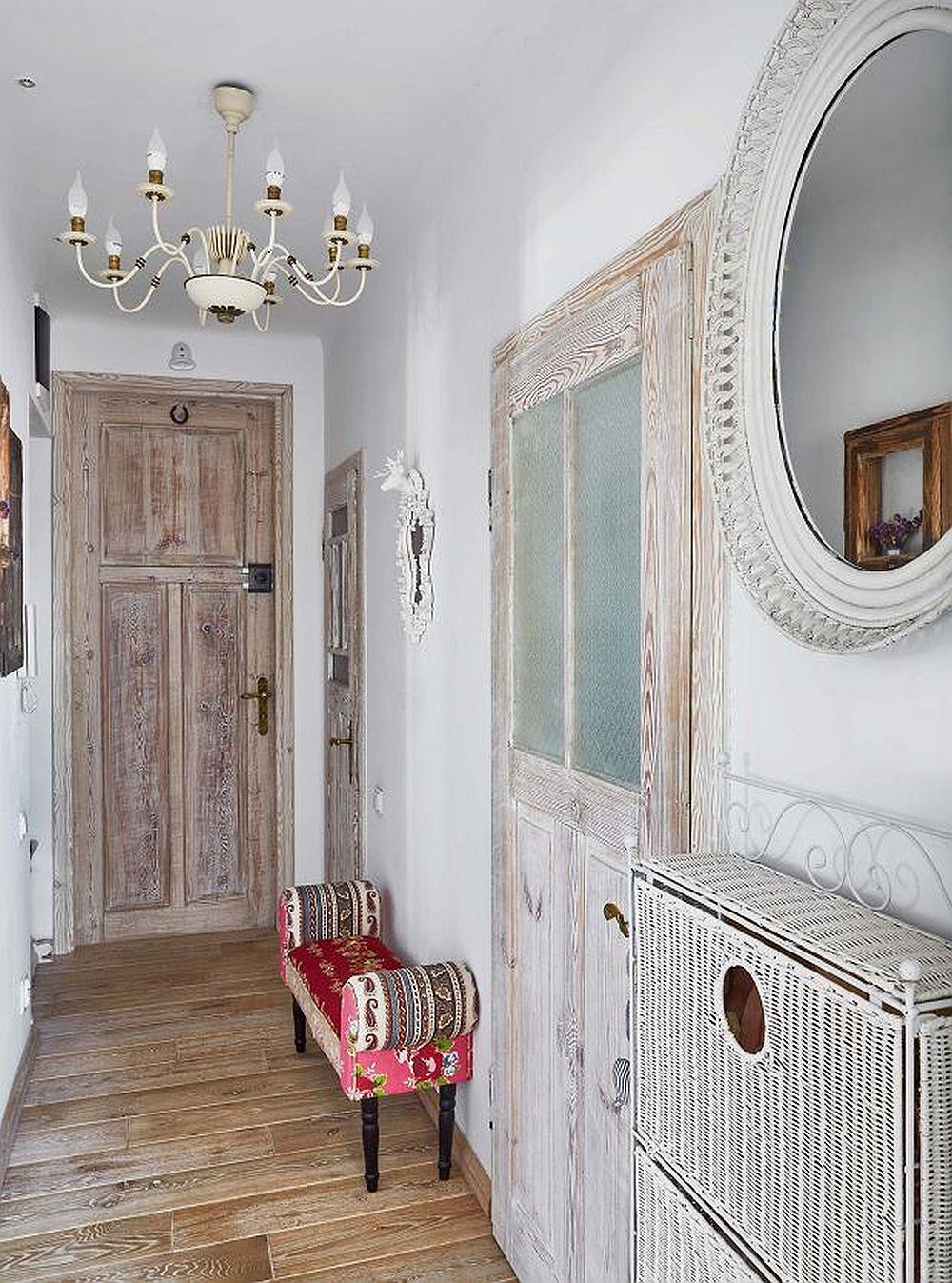 Stilul casei este marcat încă de la intrarea în casă, unde, pentru ușa principală de acces, proprietara a folosit o ușă de lemn recuperată pe care a finisat-o singură să aibă aspect antichizat. Micul taburet tapițat face parte din colecția patchwork de la kika, iar candelabrul și oglinda au fost cumpărate de la piețele de vechituri și recondiționate.