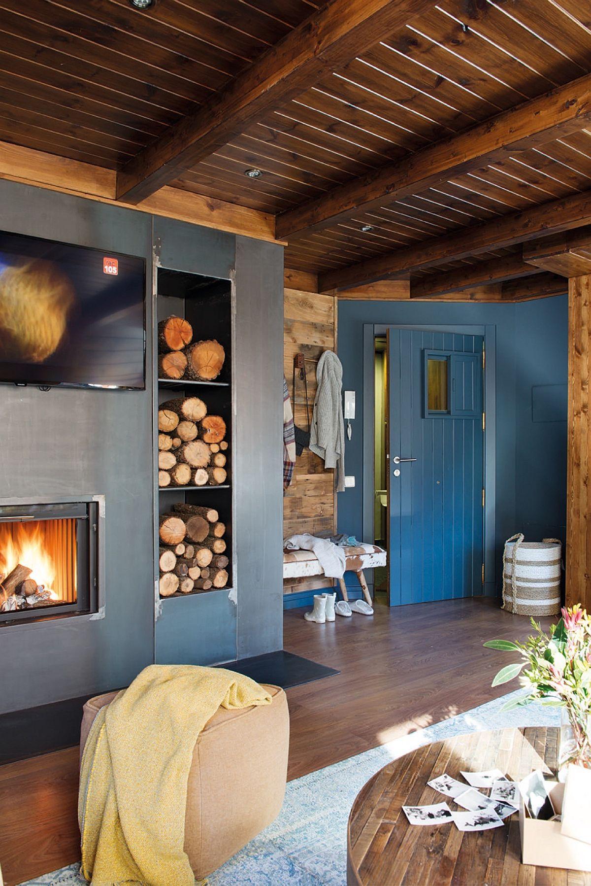 Intrarea în zona de zi coincide cu cea în cabană, unde lemnul domină spațiul. Dar cu ce poți asorta suprafețele din lemn de nuanță închisă? Cu alte tonuri închise, în special de albastru, mai ales dacă baițul lemnului este ales într-o nuanță brun roșcată. De asemenea, nuanțele de gri antracit se potrivesc și ele foarte bine.