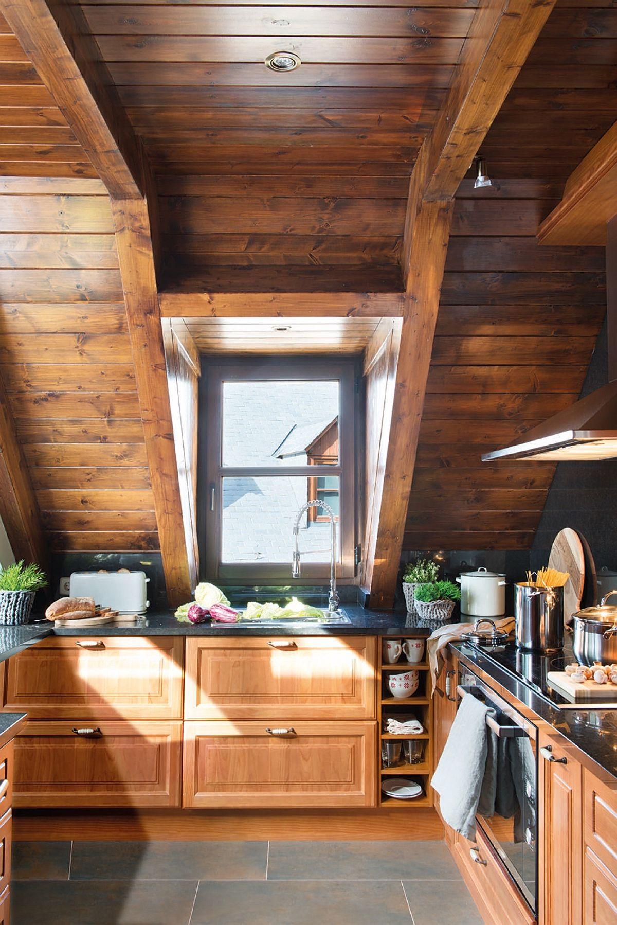Bucătăria este separată de zona de zi, dar imediat în vecnătatea acesteia. Mobila a fost realizată pe comandă în nuanță apropiată cu cea a lambriurilor care îmbracă pantele acoperișului la interior. Zona de foc este prevăzută în cea mai înaltă porțiune a acestui spațiu.