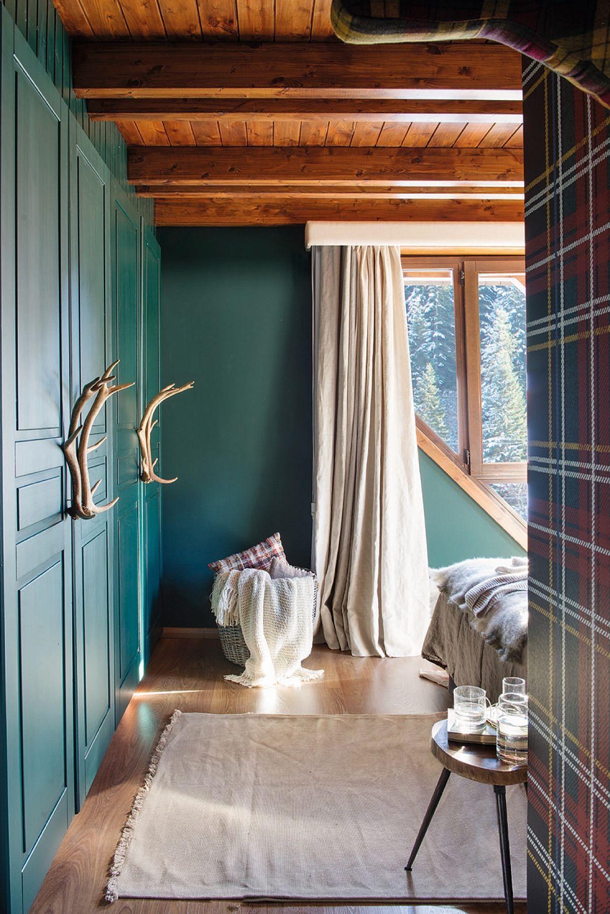 La etaj sunt dormitoarele, iar unul dintre ele, matrimonial, se remarcă prin prezența coarnelor de cerb pe post de mânere pentru dulapuri. Dar nu doar atât. Și combinația de culori și texturi este foarte plăcută, de la verdele închis al zugrăvelii la tapetul în carouri.