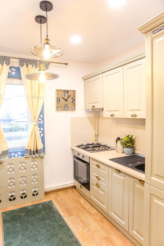 Bucătăria DUPĂ renovarea făcută de echipa Visuri la cheie. Proiectul bucătăriei este realizat de Cristina Joia. În bucătărie a fost instalată centrala termică, acum mascată în mobilier, iar sub centrală mașina de spălat rufe. Mobila a fost realizată pe comandă la Martplast, gresia de pe perete, electrocasnicele, chiuveta, perdelele și corpurile de iluminat sunt de la Dedeman.