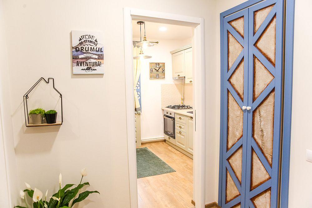La ieșirea din bucătărie se văd ușile cămării. Cristina a comandat la Martplast uși din MDF cu decoruri albastre, iar între desenele geometrice a lipit țesătură din iută, fiind proiectul ei special pentru familie.