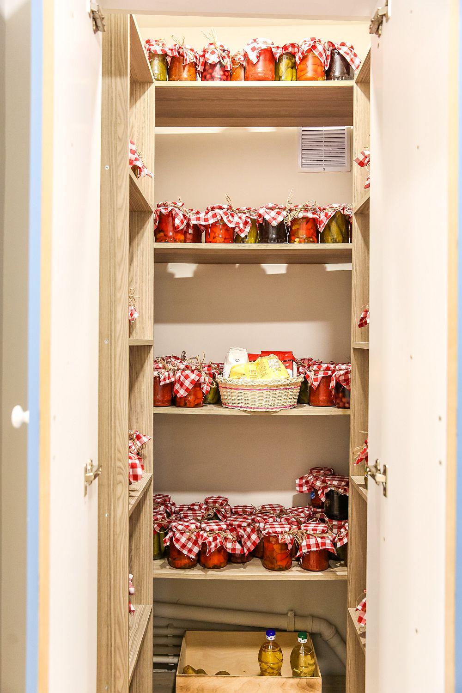 La interiorul cămării, Cristina a pus toate borcanele bunicii, dar a avut grijă să le îmbrace cu țesătură în carouri pentru a arăta frumos.