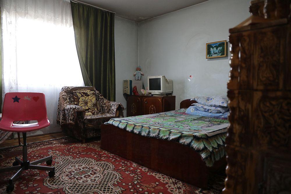 Livingul ÎNAINTE de renovarea făcută de echipa Visuri la cheie. Camera bunicii și a nepoatei, singura încălzită cu ajutorul sobei care funcționa cu lemne. Aici practic locuiau amândouă, cealaltă cameră nefiind încălzită. Camera era și loc de birou, dar și loc de dormit și de vizionat programe la tv.