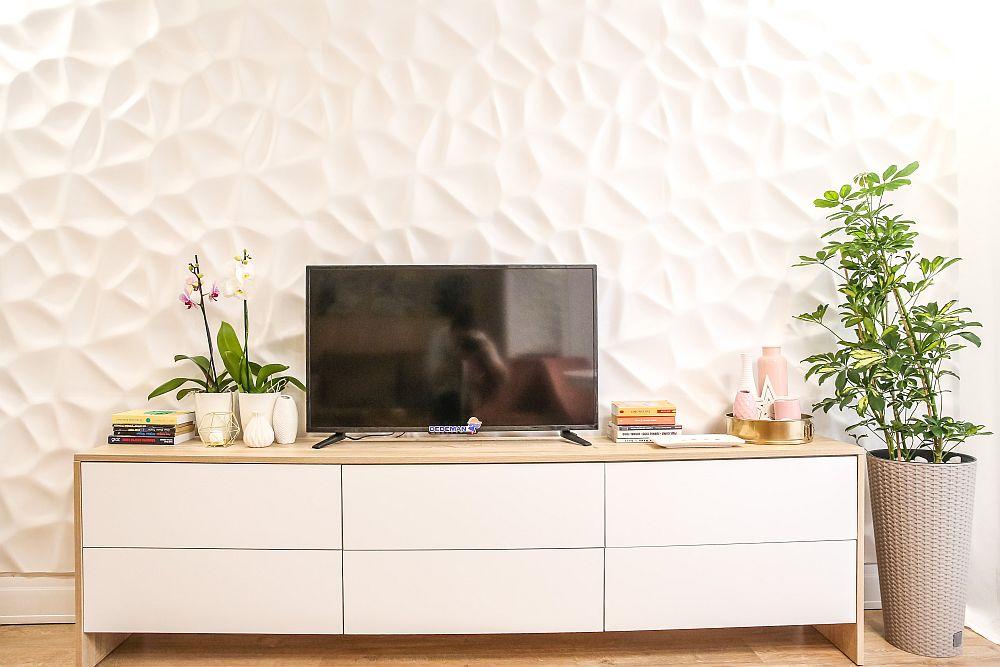 Pe peretele opus canapelei este amplasată comoda tv prevăzută numai cu sertare și este realizată pe comandă la Martplast. Planta ca și ghivechiul înalte sunt de la Dedeman, iar decorațiunile de la Pepco. Panourile 3d de pe perete sunt din ipsos și sunt furnizate de Martplast. Acestea au fost chituite cu silicon acrilic, iar peste ele s-a dat vopsea albă.