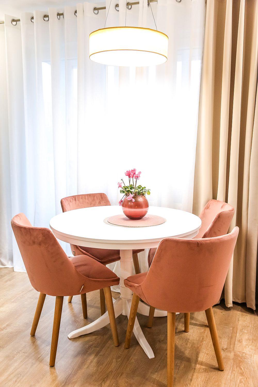 Masa (cu raza de un metru) și scaunele cu tapițerie similară catifelei sunt de la Mobila Dalin, iar corpul de ilumina de la Dedeman, la fel ca și perdelele și draperiile.