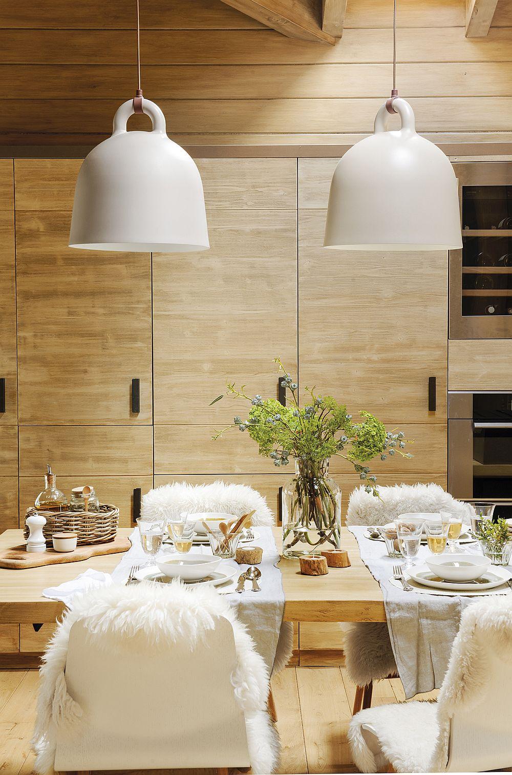 Accente de alb contează mult în atmosfera generală a zonei de zi. Astfel, corpurile de iluminat de deasupra mesei, precum și î,brăcamintea scaunelor, aduc o notă de calm într-un contrast delicat cu lemnul care predomină suprafețele.