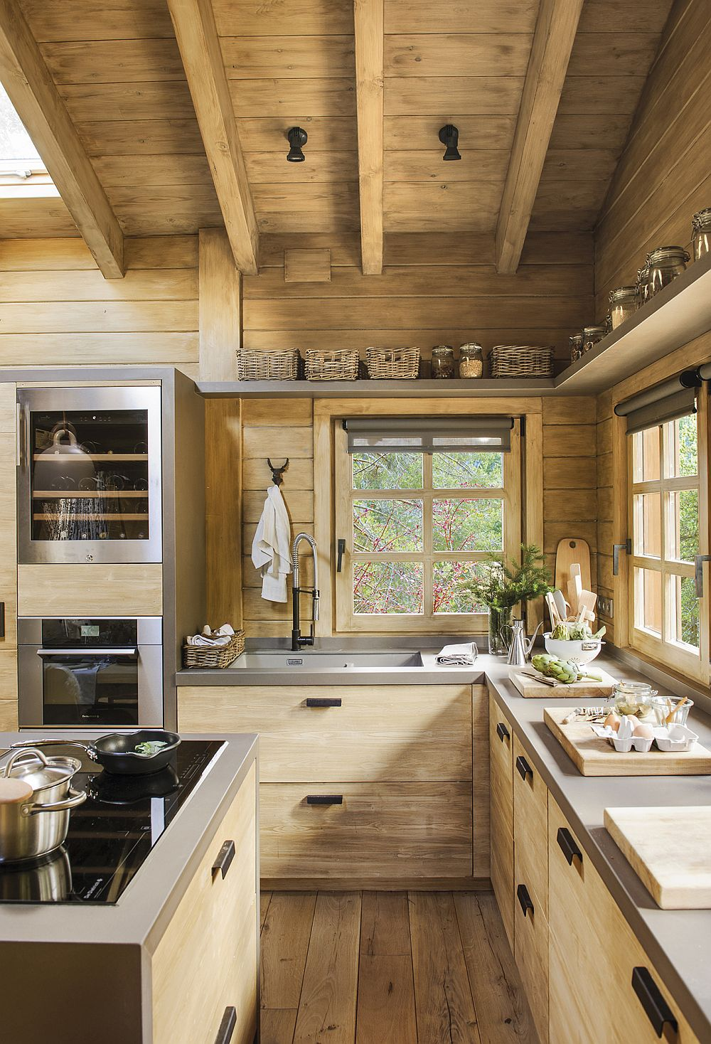 Pentru a configura o bucătărie practică și sigură, decoratoarea a prevăzut o masă insulă pe care să fie poziționată plita. Astfel, nu există niciun risc de accidente pentru că plita nu putea fi montată pe blatul din fața ferestrelor. De remarcat cât de armonios este plasat raftul de deasupra ferestrelor în legătură cu dulapurile din zona de zi în care sunt încastrate electrocasnicele.