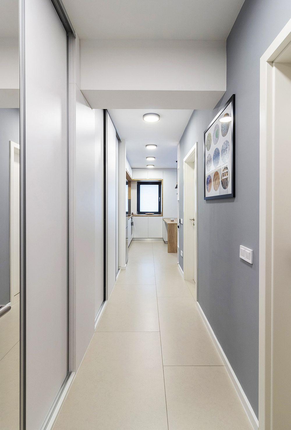 Holul suficient de lat a fost folosit pentru depozitare. Aici arhitecta a prevăzut dulapuri cu uși glisante, toate tratate în alb în acord cu plafonul. Pe partea opusă lor a folosit o nuanță de gri, care dă un aer actual, dar care rezistă foarte bine și la murdărire. În plus, griul pune în evidență golurile, adică ușile interioare și plinta, ceea ce conferă un aer elegant.