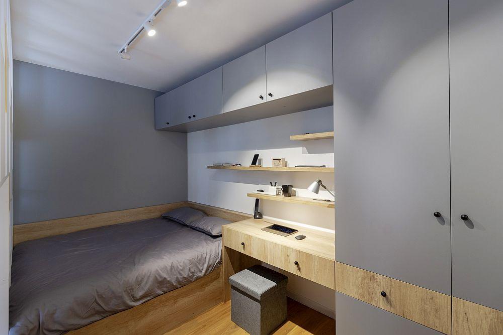 Finisajele folosite aici sunt texturi de lemn și gri, iar fiecare spațiu a fost folosit la maximum. De remarcat detaliul de la nivelul mobilierului, respectiv cum se citește linia mesei de birou continuată și prin placarea din jurul patului.