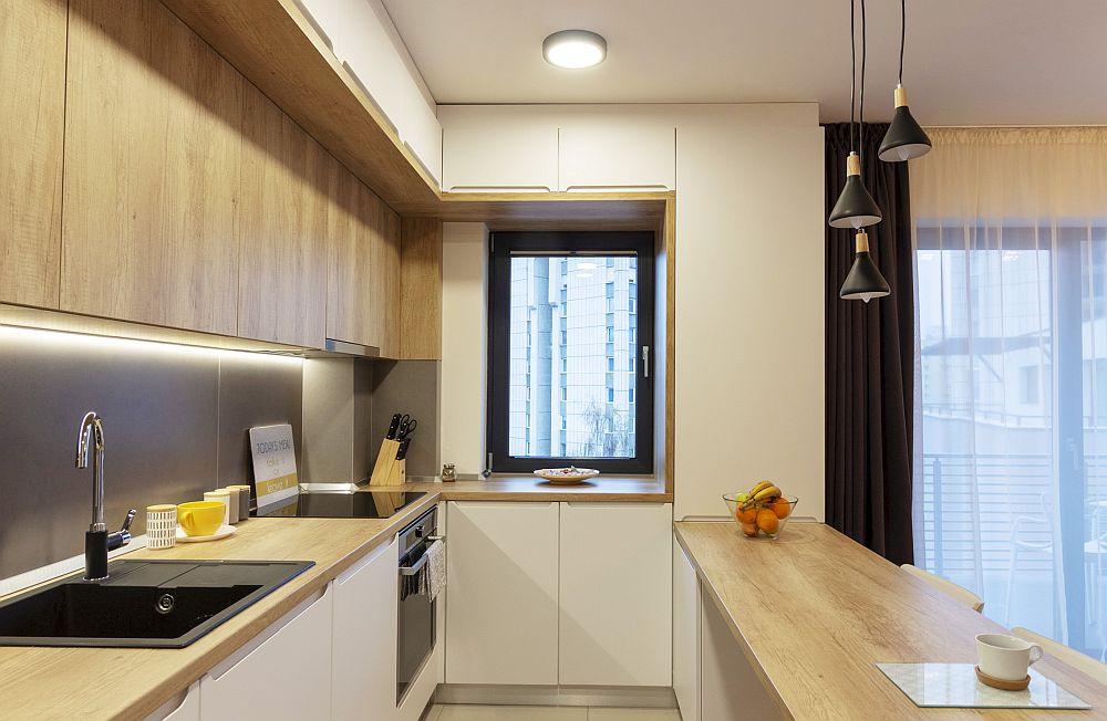 Bucătăria este mică și compactă, dar odată deschisă către living ea a fost tratată de către arhitectă mai minimalist, astfel ca dotările și electrocasnicele să nu iasă în evidență. Arhitecta a folosit texturi calde, similare lemnului, dar și iluminat deasupra blatului.