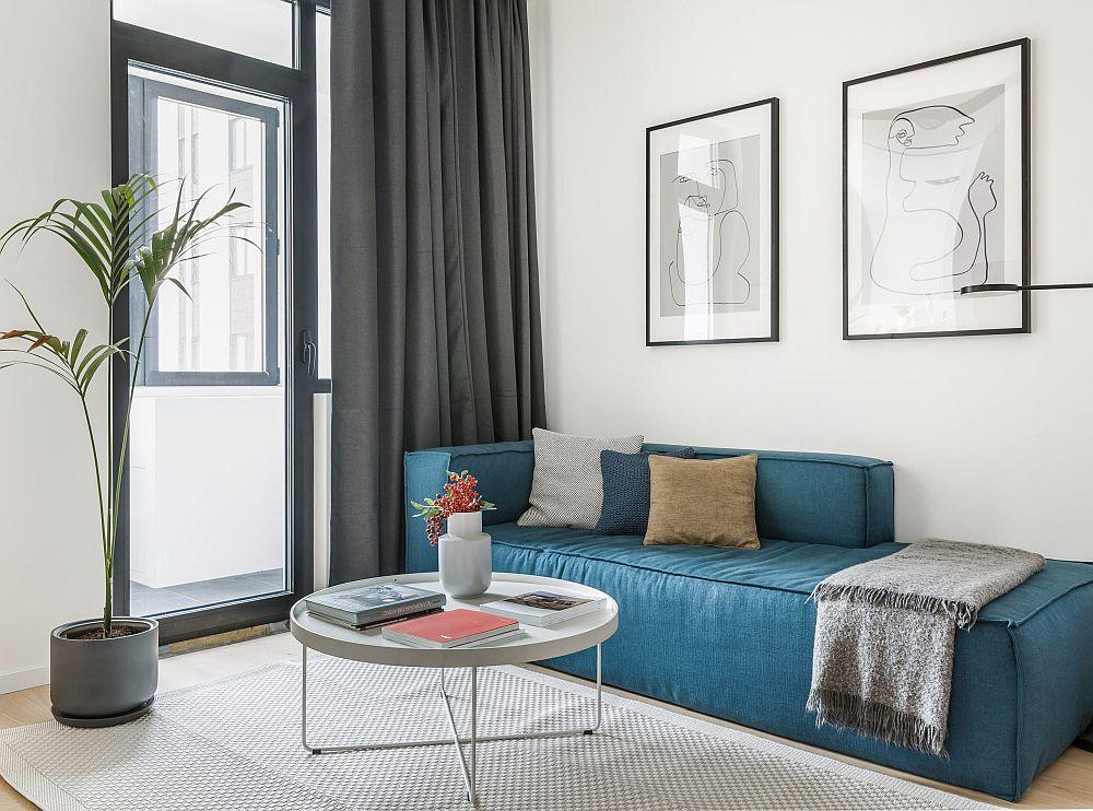 Într-un spațiu mic o canapea fără brațe în laterale este mai potrivită pentru că nu dă senzația de masivitate și oferă mai multe locuri de ședere. Modelul similar de canapea găsești la Mobila Dalin. Masa și posterele sunt de la Ikea.