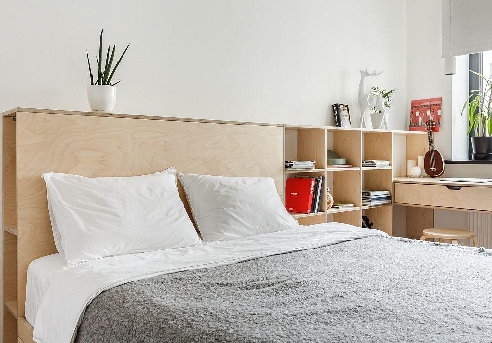 Tăblia patului este continuată cu biblioteca din zona de birou, totul păstrat la înălțime joasă pentru a nu încărca spațiul.