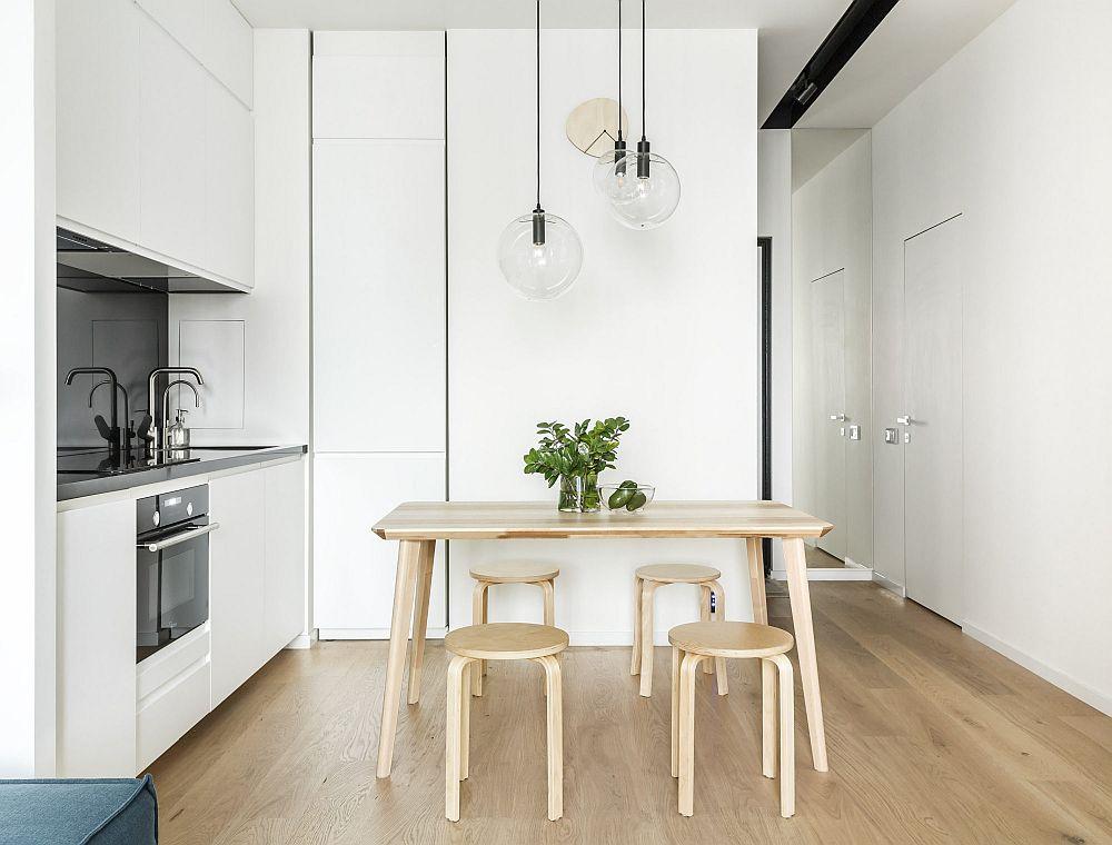 Intrarea în locuința de tip studio coincide cu intrarea în spațiul zonei de zi care include bucătăria deschisă către living. Ușa camerei de baie este în plan cu peretele, ceea ce o face să fie mult estompată ca și prezență. Totul tratat pe alb cu o oglindă poziționată strategic lângă ușa de intrare și accente de negru la nivelul corpurilor de iluminat și al blatului de bucătărie.