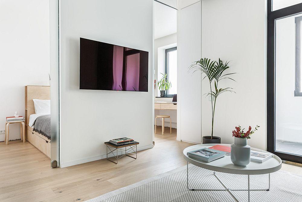Locul de tv este fără obișnuita comodă, iar peretele pe care este poziționat televizorul ascunde patul. De o parte și de alta a peretelui sunt uși glisante din sticlă sablată. Către dormitor și balcon a mai fost folosit un spațiu de depozitare, dar este închis, astfel ca spațiul să rămână cât mai simplu, curat și aerisit.