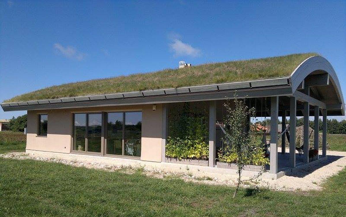 Model de casă din panouri de paie construită cu acoperiș verde.