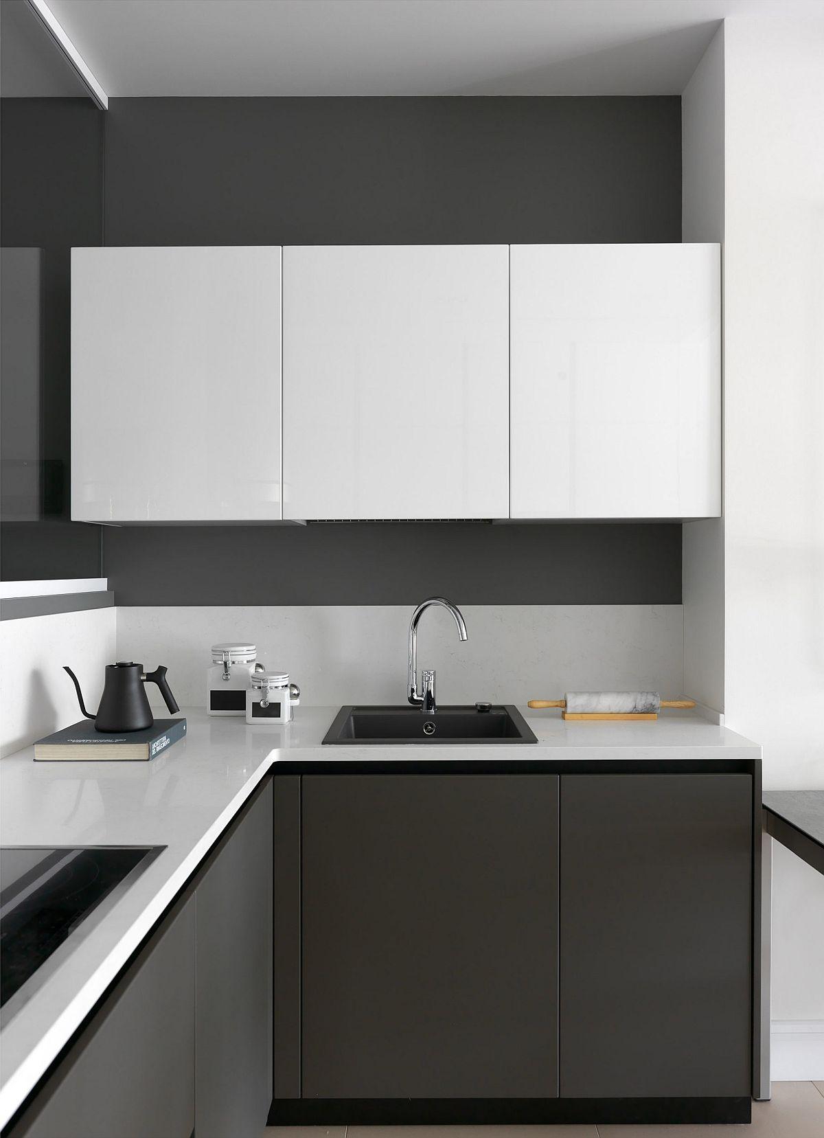Bucătăria este tratată minimal, majoritatea corpurilor de depozitare fiind situate pe partea opusă, către hol. Pereții din bucătărie, ca și corpurile joase au fost alese în nuanțe închise de antracit. Aceeași nuanță închisă este folosită și pentru pereții holului, ceea ce conferă o senzație de profunzime a spațiului, având în vedere că bucătăria este separată față de hol cu un panou de sticlă. Sticla este fixată pe blatul de lucru și în plafon.