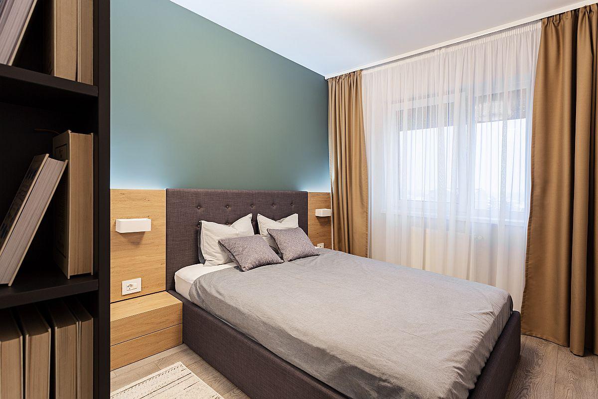 Dormitorul matrimonial este simplu, dar plăcut amenajat într-un contrast de culori cald-rece. Patul de la IKEA a fost integrat într-un ansamblu realizat pe comandă, respectiv completare de tăblie cu noptiere și iluminat local cu aplice integrat. Totul făcut după proiectul arhitecților.