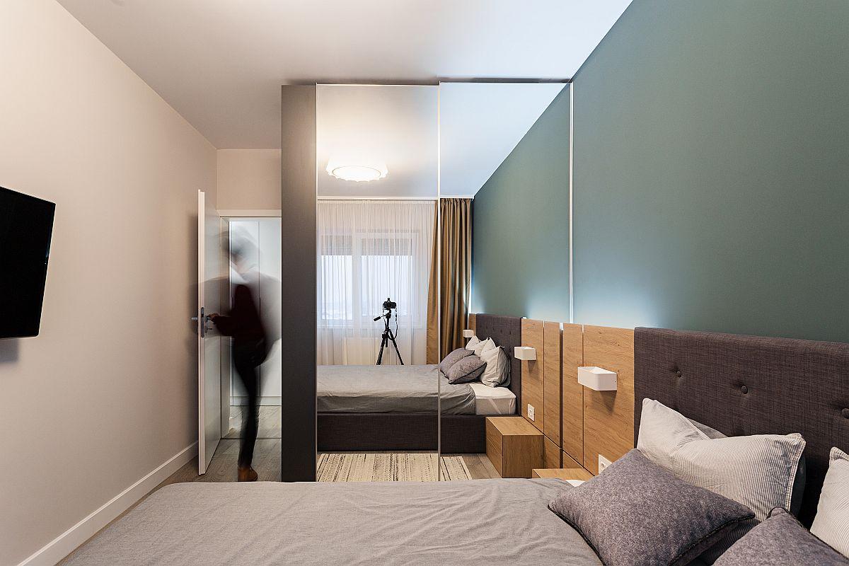 Dulapul din dormitorul matrimonial, gândit pe verticală până sus în tavan, are fețele cu oglinzi pentru ca spațiul mic să nu se simtă claustrofobic. Peretele din fața patului a fost lăsat simplu, liber, cu televizorul suspendat pentru a nu încărca spațiul.
