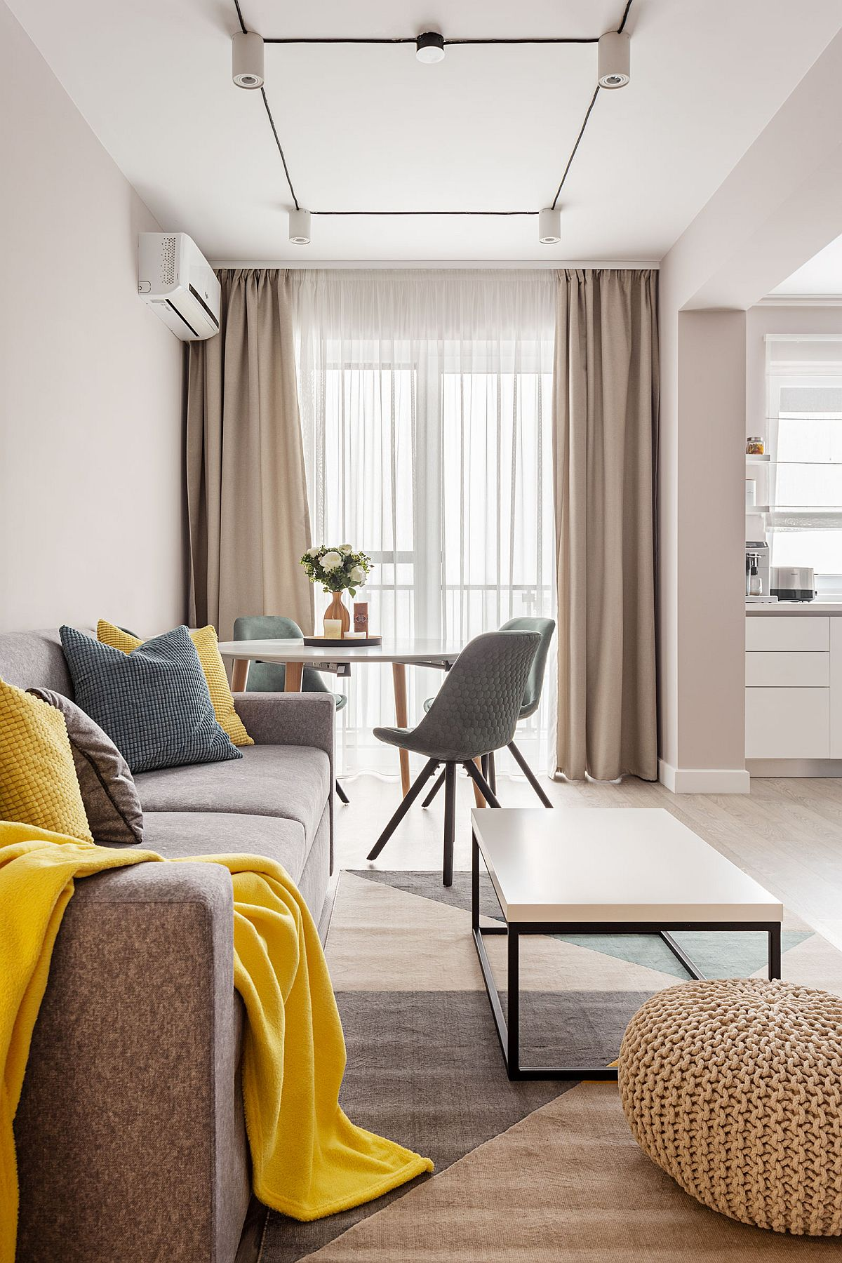 Spațiul zonei de zi, care este lung și îngust, a fost gândit pentru loc de conversație cu canapea, dar și loc de masă (sufragerie). Nuanțele pe suprafețe mari sunt neutre, in gama griurilor calde, completate cu accente de culoare prin obiecte mici de la perne decorative la tapițeria scaunelor.