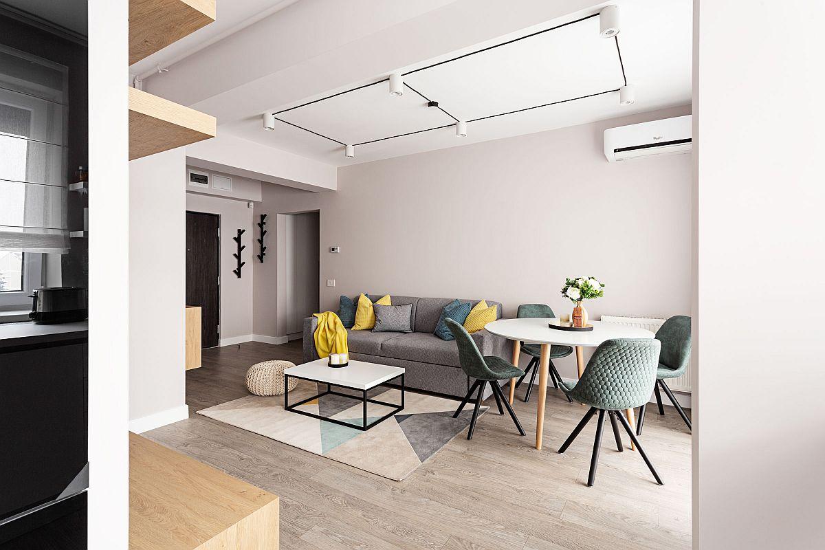Intrarea în locuință se face printr-un mic hol deschis către zona de zi, respectiv living care comunică cu bucătăria.