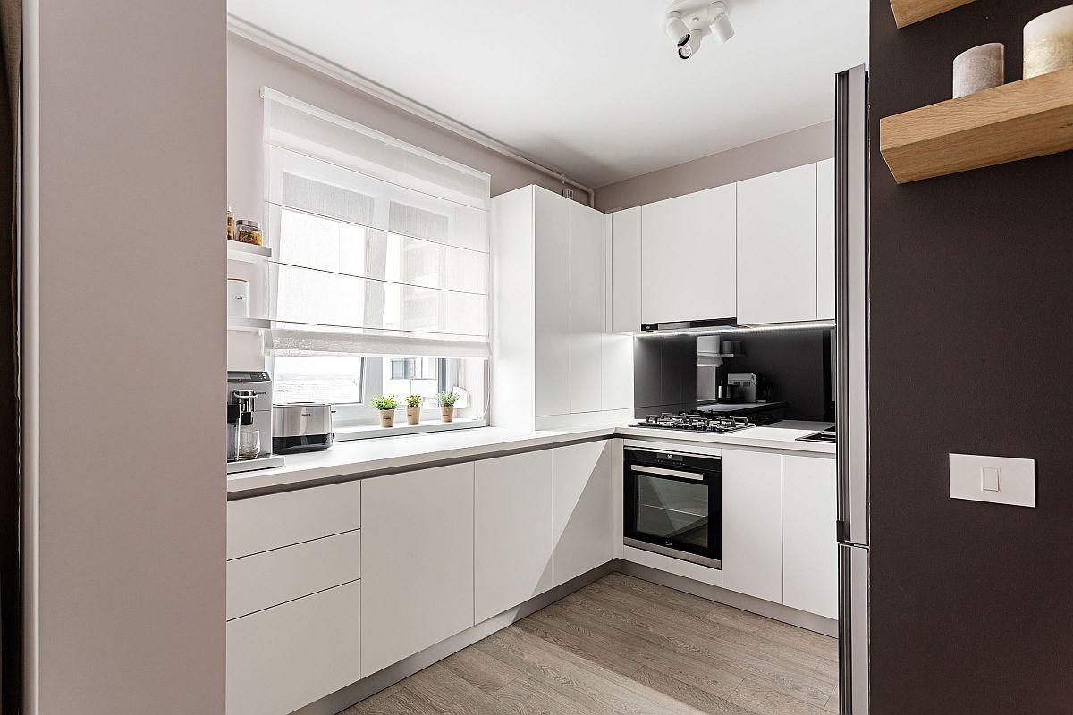 Toată mobila de bucătărie este albă pentru ca spațiul mic, dar parțial vizibil din living să nu iasă în evidență, ci să dea un plus de luminozitate. Ca atare ușile dulapurilor și sertarelor sunt prevăzute fără mânere, cu sisteme push, pentru a atenua caracterul tehnic al bucătăriei. Centrala termică este mascată prin mobilier care coboară la nivelul blatului ce se întoarce sub fereastră. De asemenea, caloriferul este integrat în mobilierul de sub fereastră.