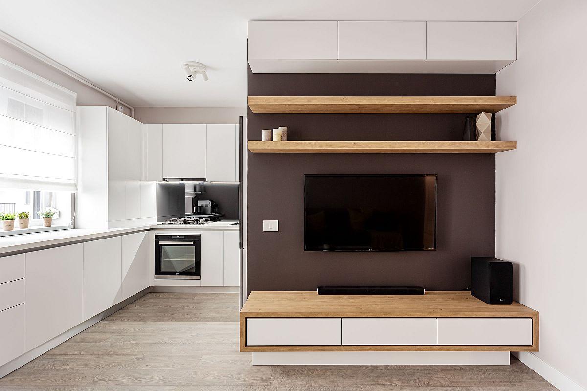 Locul de tv este configurat astfel încât să mascheze parțial bucătăria și mai ales combina frigorifică voluminoasă. Arhitecții au prevăzut o nuanță închisă pe zona de perete pe care este suspendat televizorul pentru a integra mai ușor culoarea închisă a acestuia. Comoda de sub televizor este suspendată pentru ca pardoseala să fie liberă, ceea ce dă impresia de spațiu mai generos.