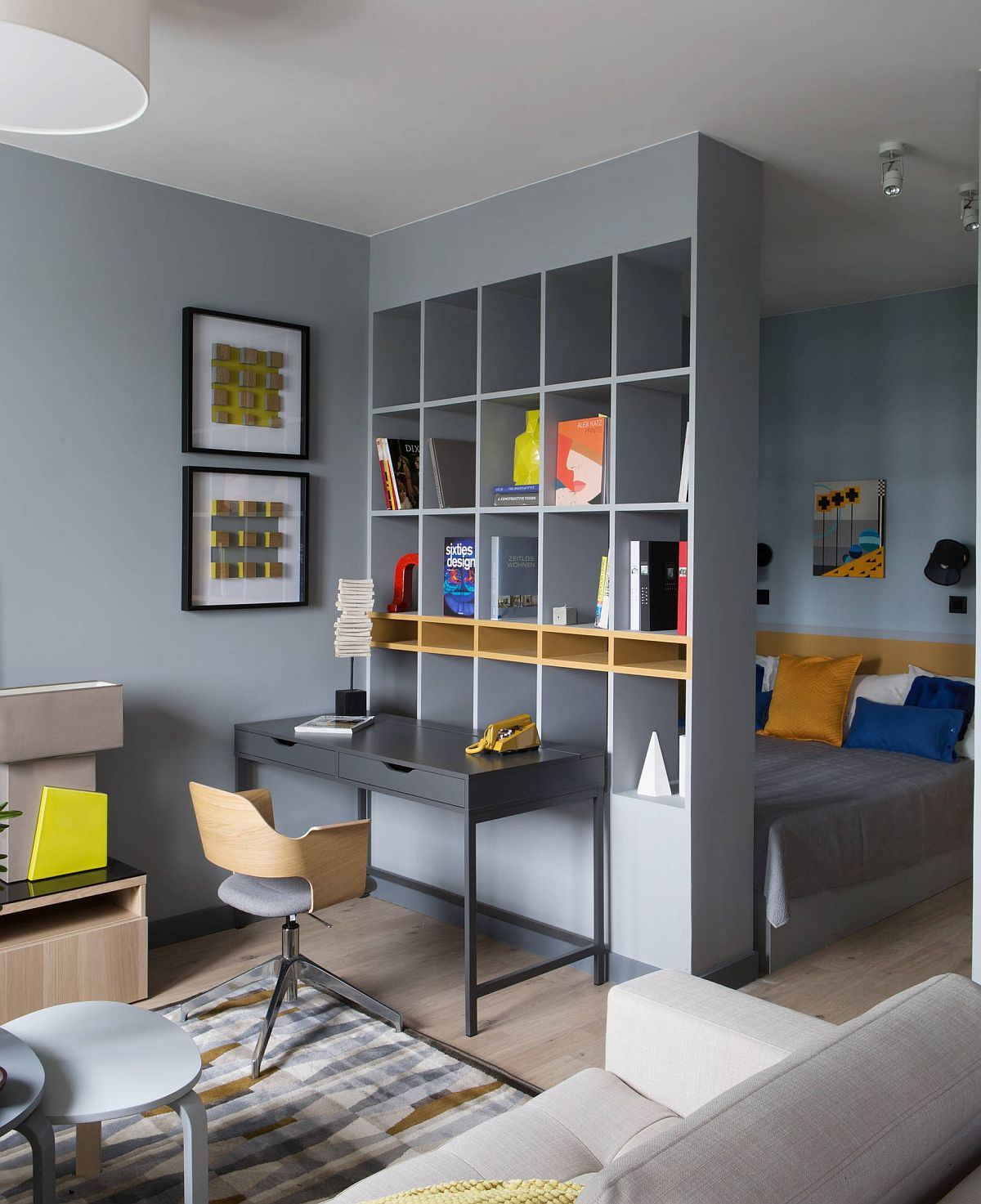 Locul de pat din garsonieră este separat prin intermediul unei biblioteci configurată până în tavan și vopsită în culoare similară nuanței de pe pereți. În fața bibliotecii a fost gândit locul de birou. Mobila aleasă pentru birou este una cu design grafic, pentru a nu încărca spațiul.