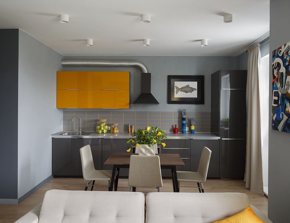 Bucătăria are electrocasnice încorporate cu excepția hotei. Designerii au propus un mobilier minimal, cu aspect actual, mânere discrete și corpuri suspendate doar acolo unde era necesar, adică deasupra chiuvetei. În rest s-a încercat ca aspectul general al bucătăriei să fie cât mai puțin tehnic, iar corpul suspendat galben vine să dea o pată de culoare, dar și luminozitate în acest colț al locuinței.