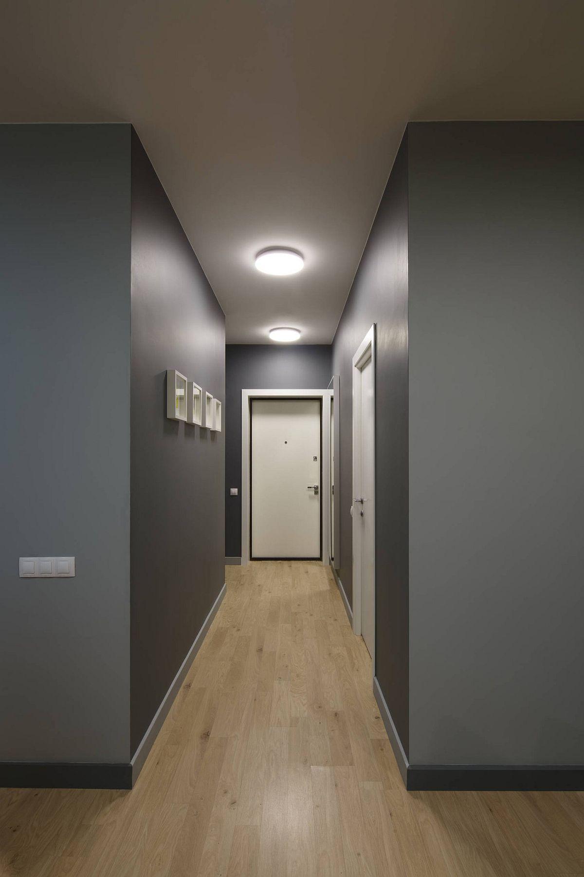 Din holul garsonierei se face accesul către baie, evident complet separată. Nuanța de gri folosită peste tot pentru pereți contrastează plăcut cu pardoseala din cu textură din lemn și ușile albe. De asemenea este o nuanță rezistentă la murdărire, inevitabilă în mediu urban.