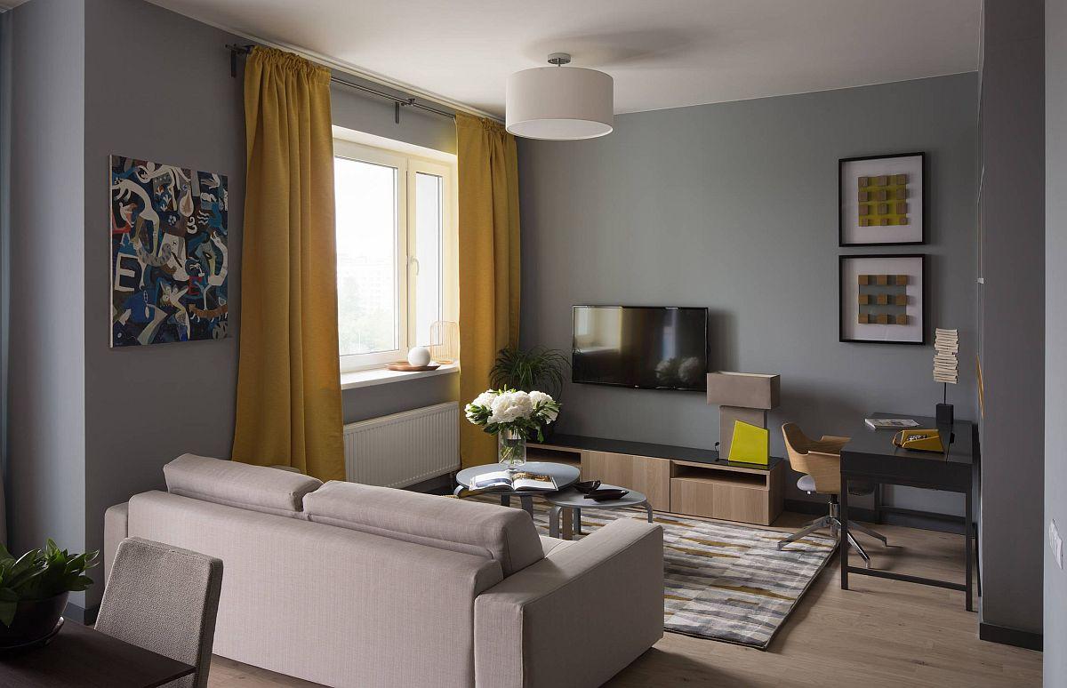 Livingul este minimal cu loc de canapea și comodă tv, dar atmosfera este creată cu ajutorul decorațiunilor textile. Draperiile încălzesc atmosfera, iar galbenul lor face încăperea mai luminoasă. De asemenea tapițeria canapelei, ca și nuanțele covorului sunt deschise, ceea ce formează un contrast plăcut cu fundalul gri al pereților.