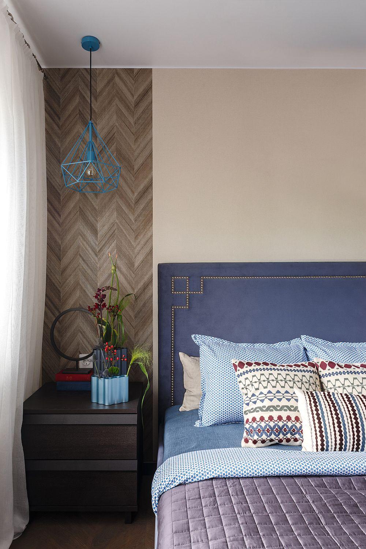 Fășia de tapet care imită desenul parchetului este prezență și în zona patului, marcând locul noptierei.