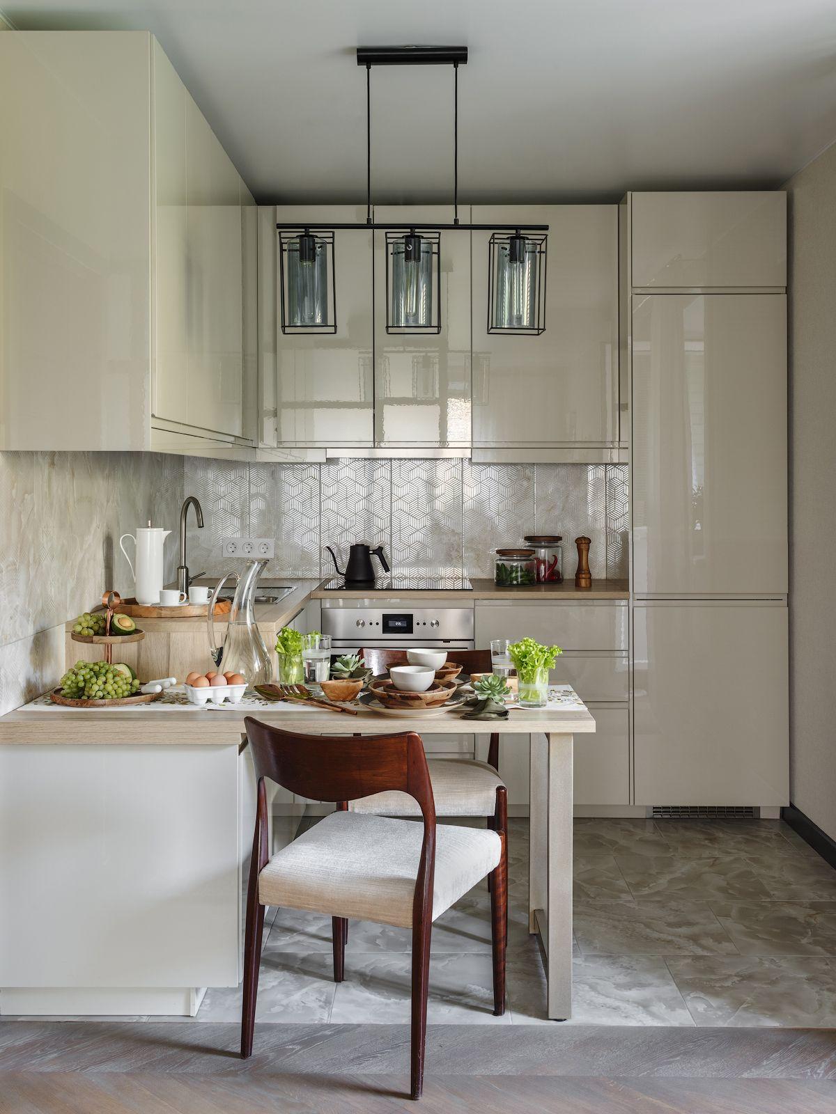 Bucătăria este bine organizată, iar designerii au ales nuanțe deschise pentru mobilier (de la IKEA) pentru a conferi mai multă luminozitate în zonă. Toate electrocasnicele sunt încorporate, iar locul de luat masa este configurat în prelungirea blatului. Deasupra acestuia a fost amplasat corpul de iluminat de la Eglo.
